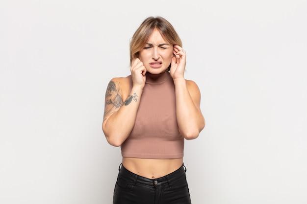 Giovane donna graziosa che sembra arrabbiata, stressata e infastidita, coprendo entrambe le orecchie con un rumore assordante, un suono o una musica ad alto volume