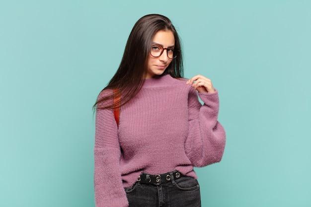 Giovane donna graziosa che sembra arrogante, di successo, positiva e orgogliosa, indicando se stessa. concetto di studente