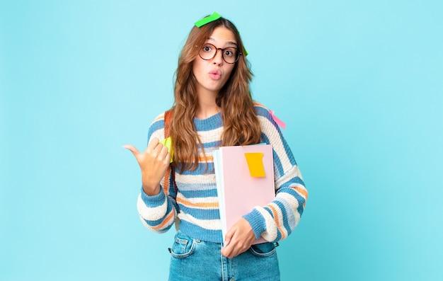 Giovane bella donna che sembra stupita per l'incredulità con una borsa e con in mano dei libri