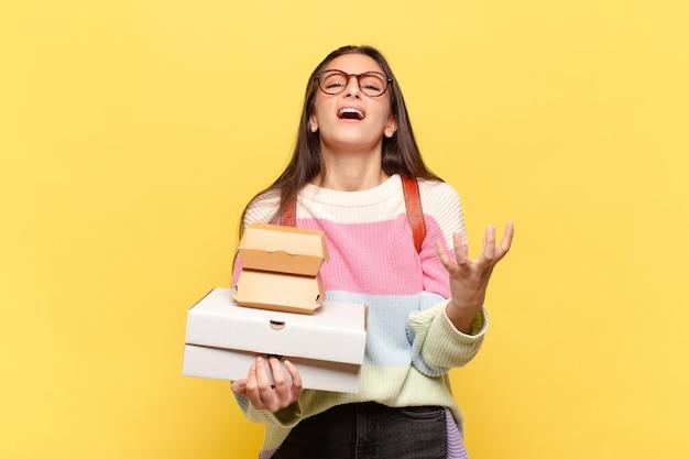 Giovane bella donna che sembra disperata e frustrata, stressata, infelice e infastidita, urla e urla. prendi un concetto di fast food