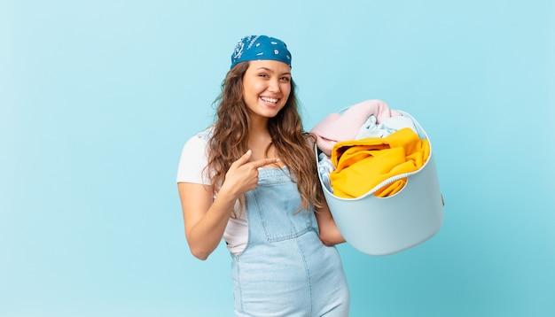 Giovane bella donna che sembra eccitata e sorpresa indicando il lato e tenendo in mano un cesto per lavare i panni