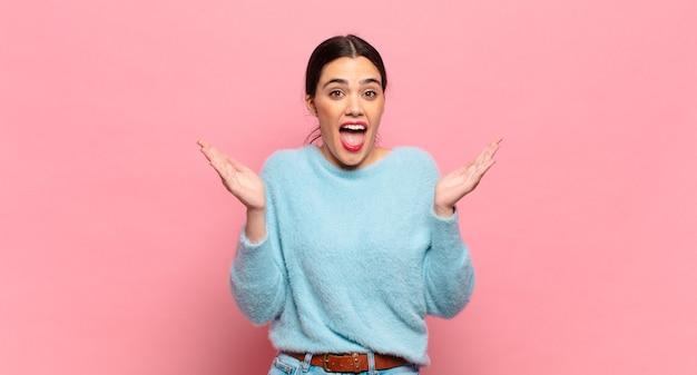 Giovane bella donna che sembra felice ed eccitata, scioccata da una sorpresa inaspettata con entrambe le mani aperte accanto al viso