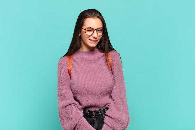 Giovane bella donna che sembra felice e amichevole, sorride e ti fa l'occhiolino con un atteggiamento positivo. concetto di studente