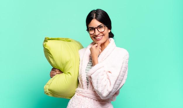 Giovane bella donna che sembra felice e sorridente con la mano sul mento, chiedendosi o facendo una domanda, confrontando le opzioni. concetto di pigiama