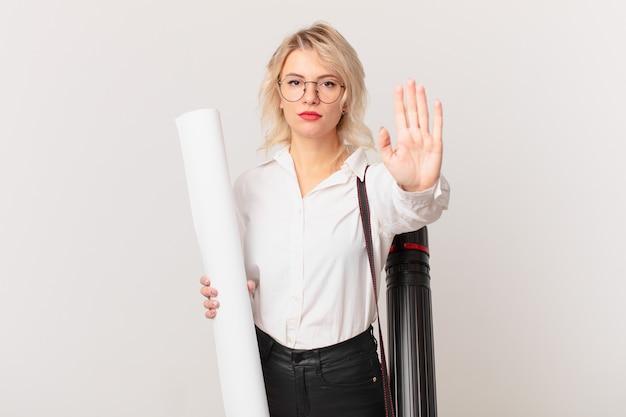 Giovane donna graziosa che sembra seria mostrando palmo aperto che fa gesto di arresto. concetto di architetto