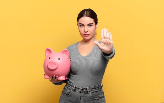 Giovane donna graziosa che sembra serio, severo, dispiaciuto e arrabbiato che mostra il palmo aperto che fa il gesto di arresto