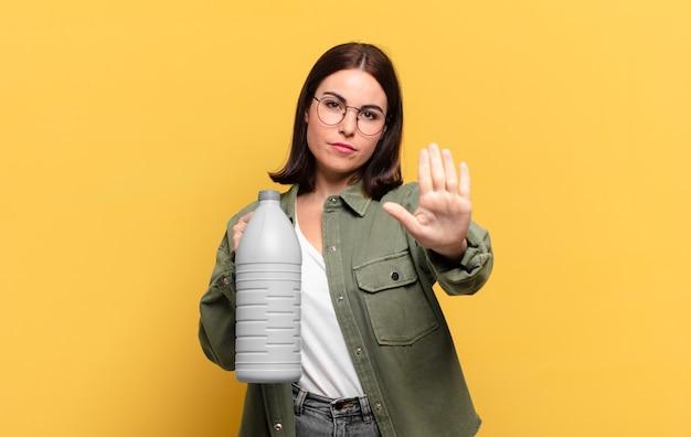 Giovane bella donna che sembra seria, severa, dispiaciuta e arrabbiata che mostra il palmo aperto che fa un gesto di arresto
