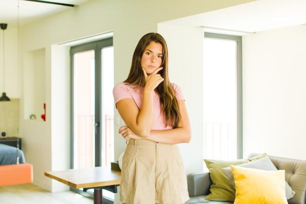 Giovane donna graziosa dall'aspetto serio, premuroso e diffidente, con un braccio incrociato e una mano sul mento, opzioni di ponderazione