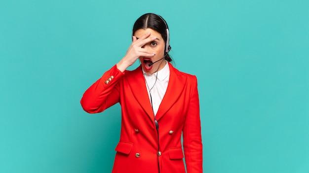 Giovane bella donna che sembra scioccata, spaventata o terrorizzata, coprendo il viso con la mano e sbirciando tra le dita. concetto di telemarketing