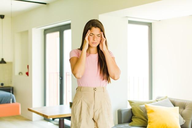 Giovane bella donna che sembra stressata e frustrata, lavora sotto pressione con un mal di testa e tormentata dai problemi