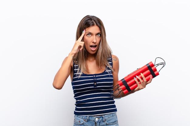 Giovane donna graziosa che sembra sorpresa con una bomba della dinamite