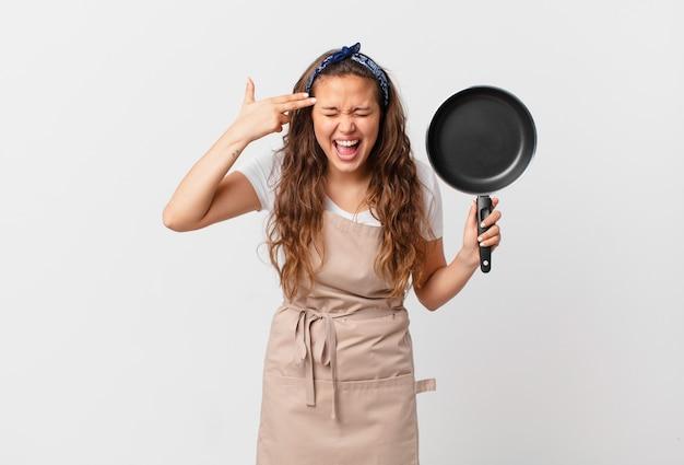 Giovane bella donna che sembra infelice e stressata, gesto suicida che fa segno di pistola concetto di chef e tiene in mano una padella