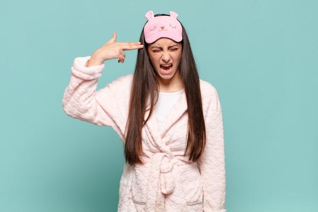 Giovane donna graziosa che sembra infelice e stressata, gesto di suicidio che fa il segno della pistola con la mano, indicando la testa. svegliarsi indossando il concetto di pigiama