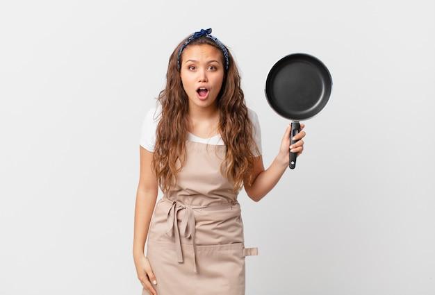 Giovane bella donna che sembra molto scioccata o sorpresa dal concetto di chef e tiene in mano una padella