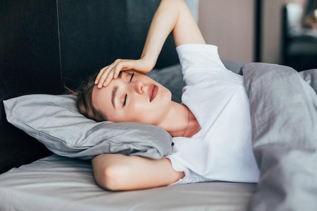 Giovane bella donna sdraiata e dorme nel suo letto a casa