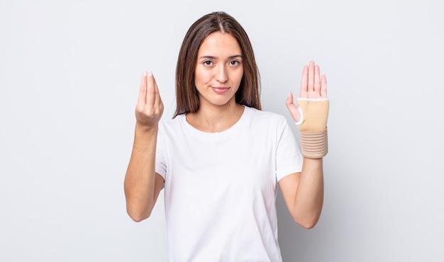 Giovane bella donna che fa un gesto di capice o denaro, dicendoti di pagare. concetto di fasciatura per le mani