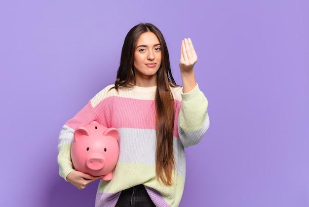 Giovane bella donna che fa un gesto di capice o denaro, dicendoti di pagare i tuoi debiti!