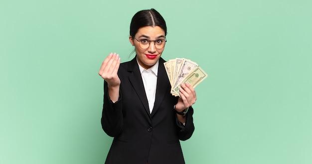 Giovane bella donna che fa un gesto di capice o denaro