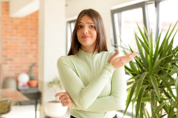 Giovane donna graziosa che fa un gesto a casa