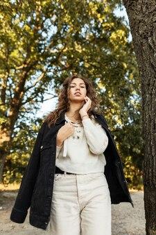 Modello di giovane donna graziosa con capelli ricci in una giacca di jeans alla moda con una perlina lavorata a maglia passeggiate nel parco e guarda la telecamera