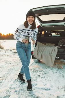 Giovane bella donna vicino a un'auto suv con bagagliaio aperto al tramonto sulla spiaggia del lago ghiacciato