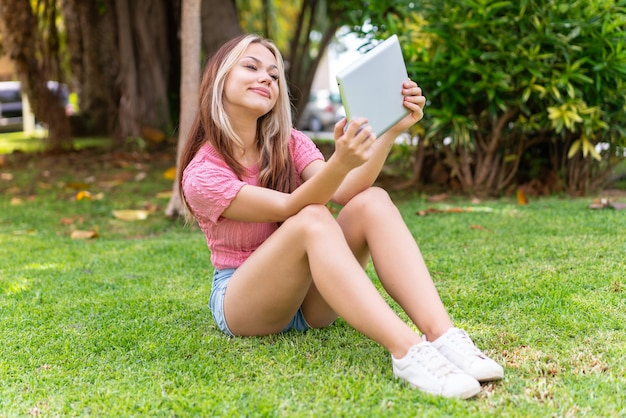 Giovane bella donna all'aperto con in mano un tablet