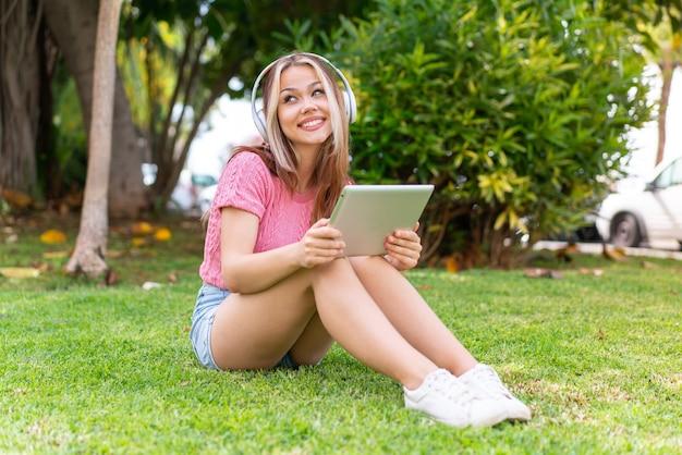 Giovane bella donna all'aperto che ascolta musica con il cellulare e felice