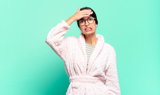 Giovane bella donna in preda al panico per una scadenza dimenticata, sentendosi stressata, dovendo coprire un pasticcio o un errore. concetto di pigiama