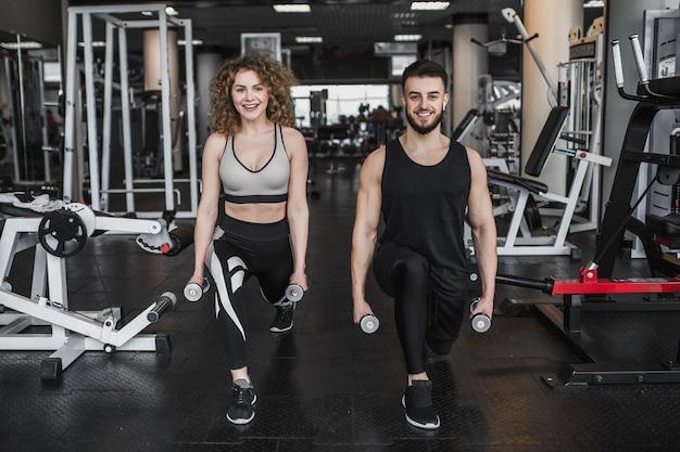 Giovane bella donna e personal trainer con squat con manubri in palestra