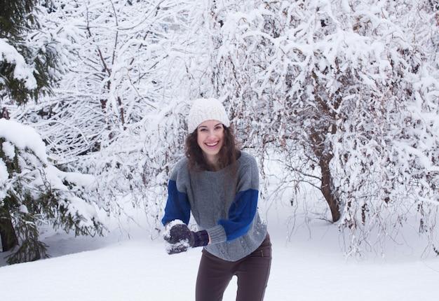 Giovane donna graziosa che gioca lotta a palle di neve in una foresta invernale