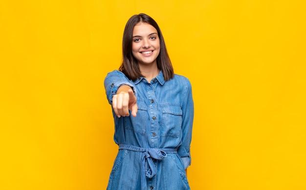 Giovane donna graziosa che punta alla telecamera con un sorriso soddisfatto, fiducioso e amichevole