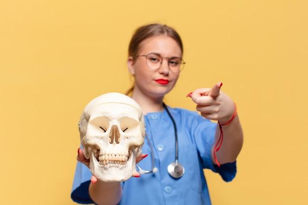 Giovane donna graziosa. gesto di puntamento infermiera concept