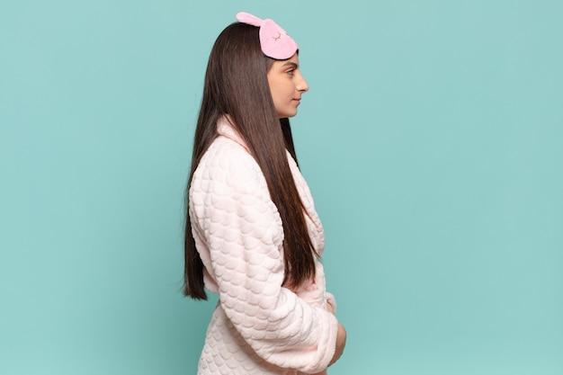 Giovane bella donna in vista di profilo che cerca di copiare lo spazio davanti a sé, pensando, immaginando o sognando ad occhi aperti. svegliarsi indossando il concetto di pigiama