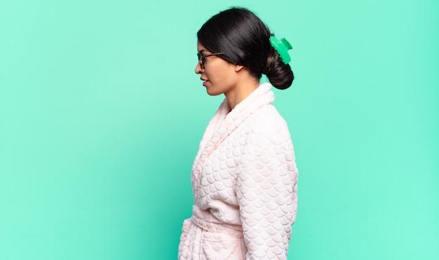 Giovane bella donna in vista di profilo che cerca di copiare lo spazio avanti, pensando, immaginando o sognando ad occhi aperti. concetto di pigiama