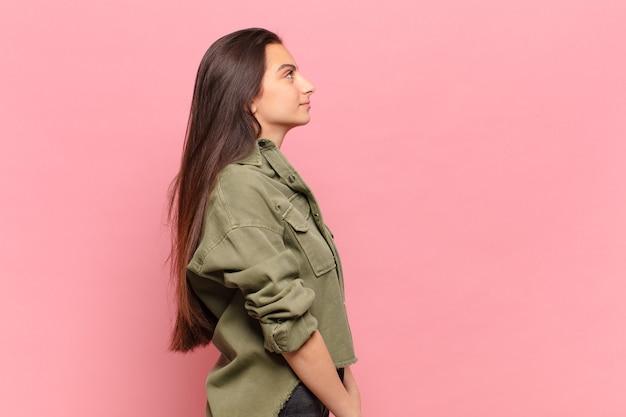 Giovane donna graziosa sulla vista di profilo che cerca di copiare lo spazio davanti, pensare, immaginare o sognare ad occhi aperti