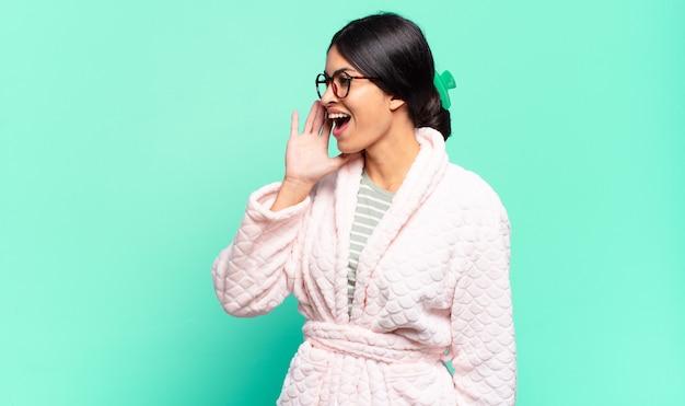Vista di profilo della giovane donna graziosa, che sembra felice ed eccitata, gridando e chiamando per copiare lo spazio sul lato