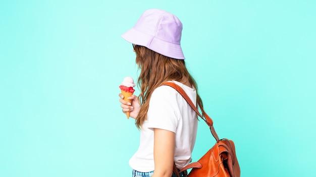 Giovane bella donna in vista di profilo pensando, immaginando o sognando ad occhi aperti con in mano un gelato. concetto di estate