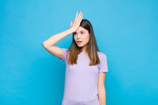 Giovane donna graziosa che solleva il palmo alla fronte pensando oops, dopo aver fatto uno stupido errore o aver ricordato, sentendosi muto contro il muro blu