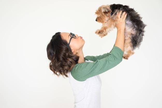 Giovane donna graziosa che alza yorkshire terrier