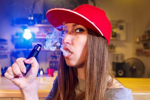 La giovane donna graziosa in spiritello malevolo fuma una sigaretta elettronica al negozio del vape. avvicinamento.