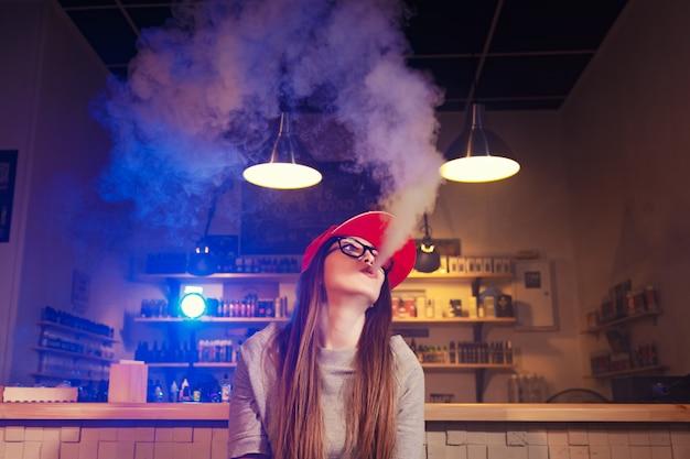 La giovane donna graziosa in spiritello malevolo fuma una sigaretta elettronica al negozio del vape
