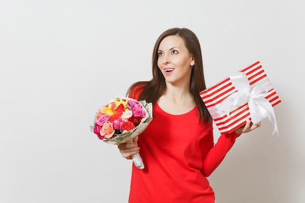Giovane donna graziosa in vestiti rossi che tengono il mazzo di bei fiori delle rose, scatola attuale con il regalo isolato su fondo bianco. san valentino, concetto di festa di compleanno della giornata internazionale della donna