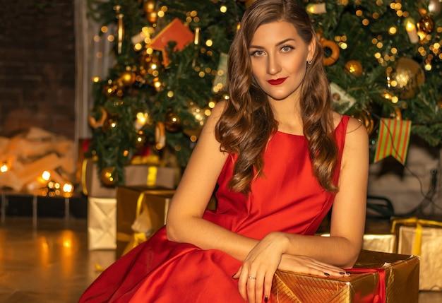 Giovane donna graziosa in primo piano vestito rosso sotto l'albero di abete con decorazioni natalizie.