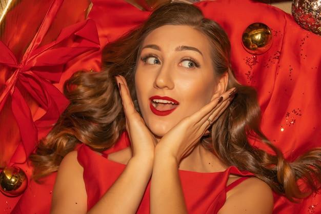 Giovane donna graziosa in primo piano vestito rosso con decorazioni natalizie.