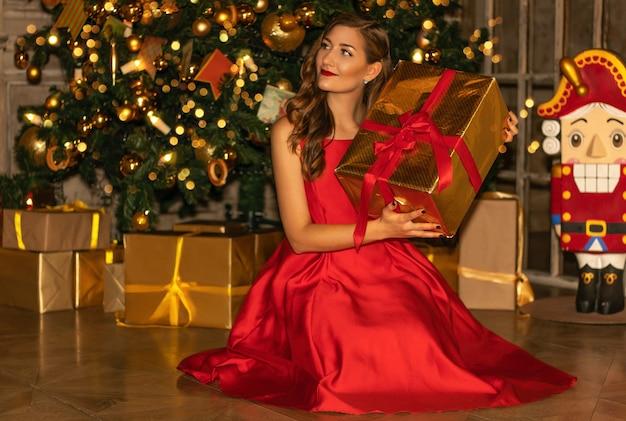 Giovane donna graziosa in primo piano del vestito rosso con le decorazioni di natale