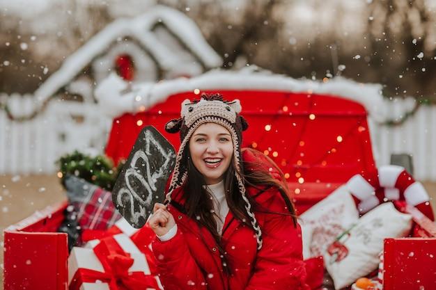 Giovane bella donna in giacca invernale rossa e cappello lavorato a maglia come un toro in posa con la targhetta 2021 nell'auto rossa aperta con decorazioni natalizie. nevicando.