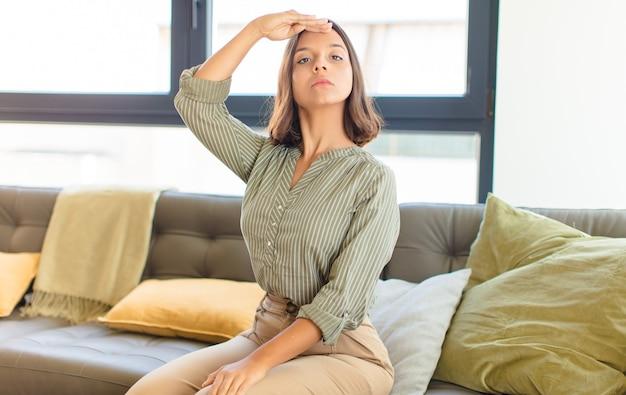Giovane donna graziosa che si distende a casa su un divano