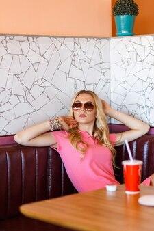 Giovane bella donna che riposa al bar e beve cola
