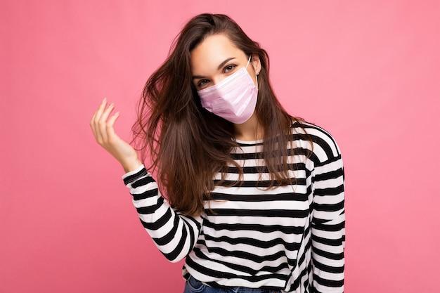 Giovane bella donna con maschera rosa protettiva riutilizzabile contro il virus sul viso