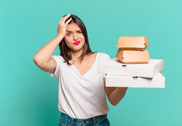 Giovane bella donna espressione triste e tenendo pizze da asporto
